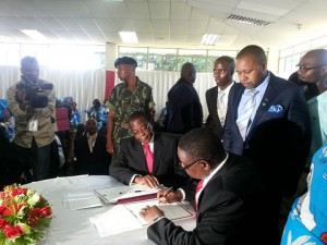 Peter signs the forms while running mate, Chilima, and EC chair, Mbendera, looks on